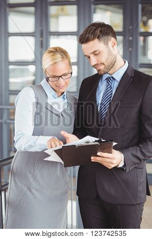 Business people discussing over documents while standing in office