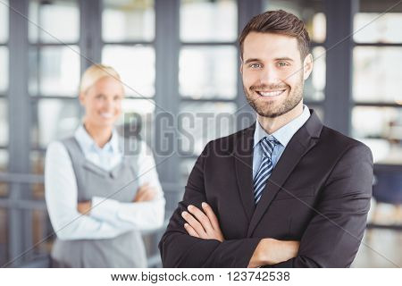 Portrait of happy businesman with arms crossed while female colleague in background