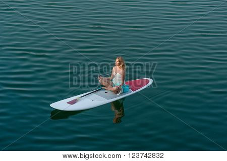 SUP bride Yoga Meditation. Girl in white dress meditating, sitting on a paddle board on water