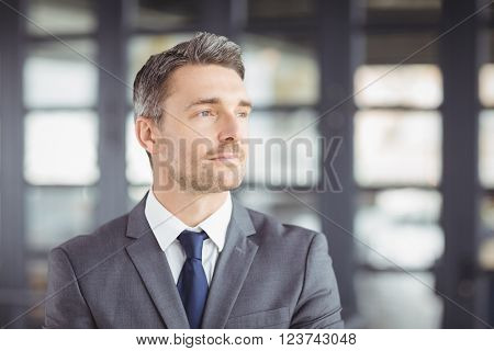 Close-up of handsome businessman looking away while standing in office
