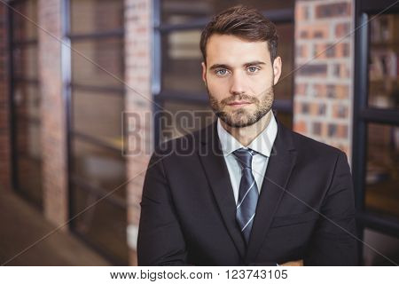 Close-up portrait of confident businessman standing in office