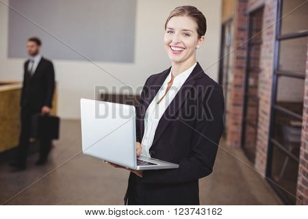 Portrait of beautiful businesswoman using laptop while standing in office