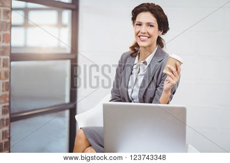 Portrait of businesswoman holding disposable cup while sitting on laptop desk