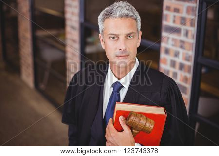 Portrait of confident male lawyer with gavel and red book standing in office