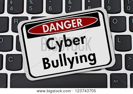 Cyber Bullying Danger Sign A white danger sign with text Cyber Bullying on a keyboard