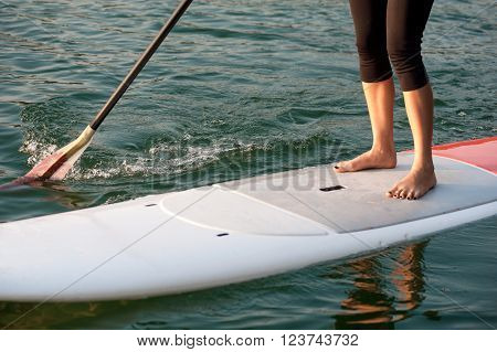 front view of a young woman paddleboarding in sports clothing SUP
