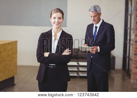 Happy businesswoman with male colleague standing in background