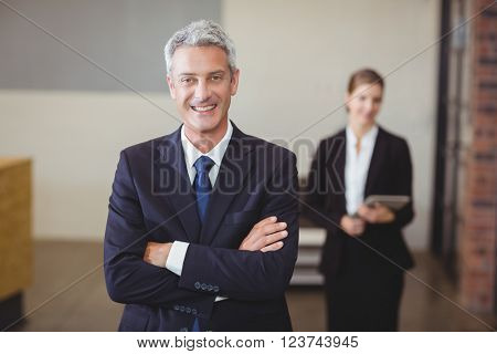 Portrait of businessman with arms crossed while female colleague standing in background