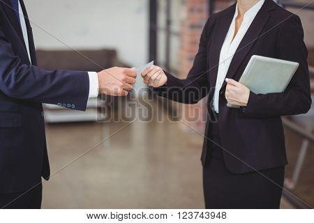 Midsection of businesswoman giving business card to client in office