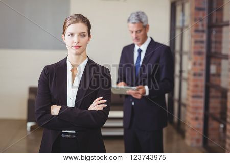 Confident businesswoman with arms crossed while male colleague standing in background