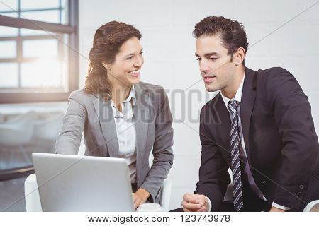 Happy business people using laptop while discussing at office