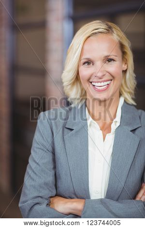 Portrait of smiling businesswoman with arms crossed while standing in office