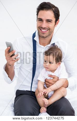 Portrait of smiling father holding mobile phone with baby at home