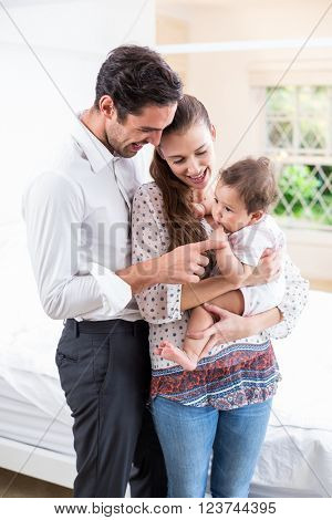 Smiling parents playing with baby at home