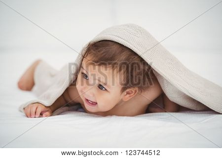 Cute baby lying under blanket at home
