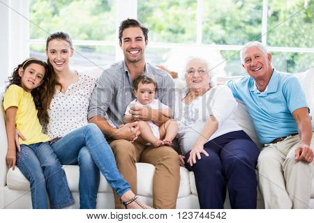 Portrait of smiling family with grandparents while sitting on sofa at home