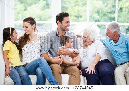 Happy family with grandparents sitting on sofa at home