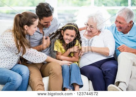 Smiling multi-generation family sitting on sofa at home