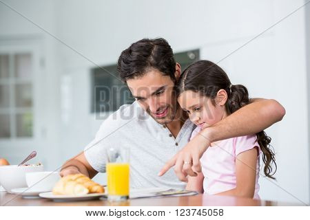 Father and daughter reading newspaper at breakfast table