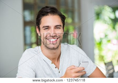 Portrait of smiling man holding smartphone at home