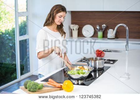 Beautiful young woman cooking food at home