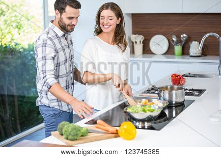 Man helping woman in cooking food at home