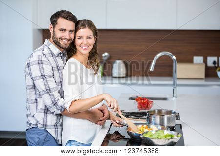 Portrait of man embracing woman while preparing food at kitchen counter