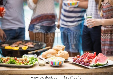 Table laid with hamburgers, fruits and barbecue for outdoors barbecue party