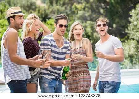 Group of friends popping a champagne bottle near pool