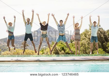 Group of friends jumping at poolside with their hands raised