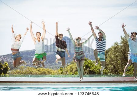 Group of friends jumping in swimming pool with their hands raised