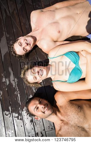 Smiling friends relaxing on wooden deck near pool