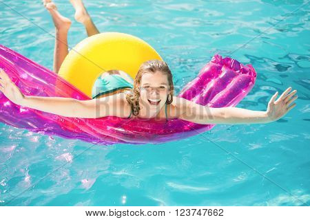 Happy woman floating on air bed in swimming pool
