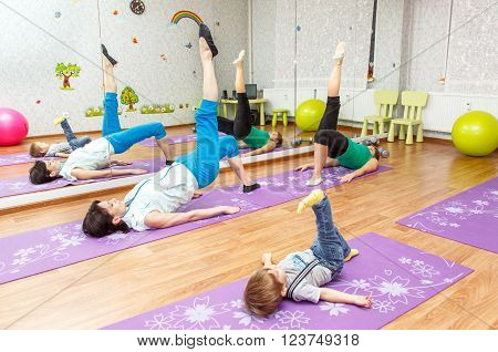 Aerobics pilates. Woman kid boy and personal instructor at gym