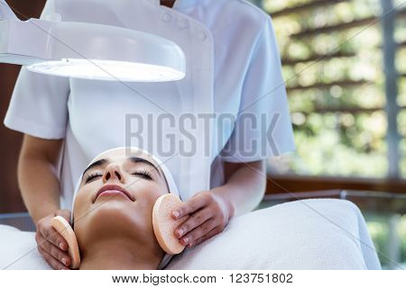 Masseuse cleaning woman face with cotton swabs at spa