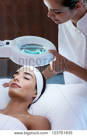 Masseuse looking at woman face at spa