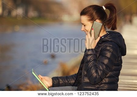 Smiling young womanstudent talking to phone taping on tablet using tablet in a city park near river.Young smiling student outdoors with tablet.Life style.City