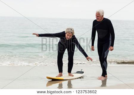 Senior man teaching woman to surf on beach