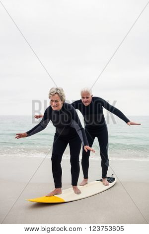 Happy senior couple surfing on surfboard on a sunny day