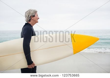 Senior woman holding surfboard on the beach on a sunny day