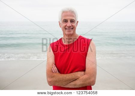 Portrait of senior man standing with arms crossed on beach on a sunny day