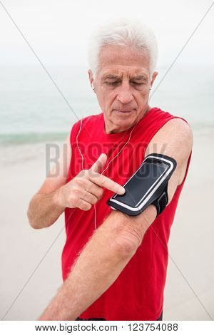 Senior man listening to music on his phone held by the arm band