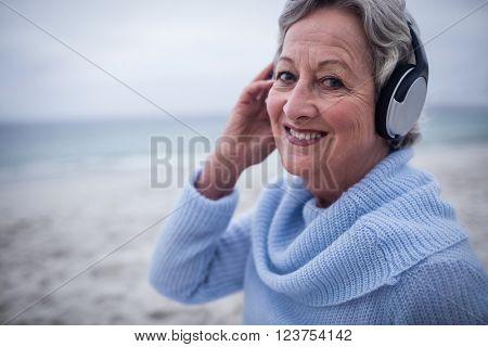 Portrait of senior woman listening to music on headphone at beach