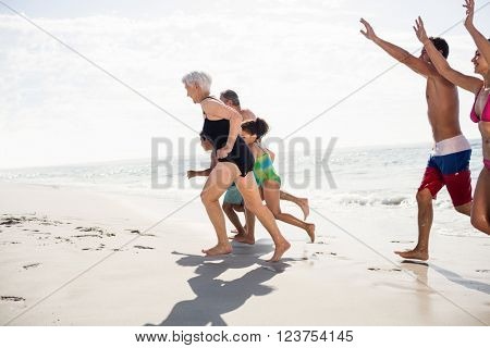 Happy family walking on beach on a sunny day