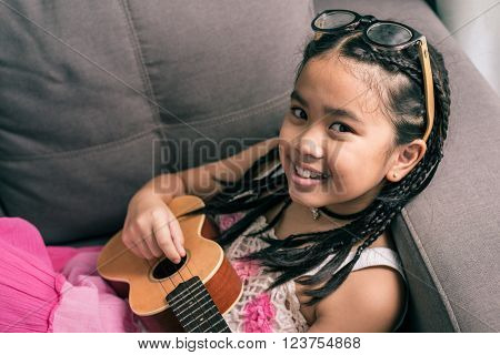 Happy smiling girl,wearing glasses,dreadlocks hair style ,learning to play music