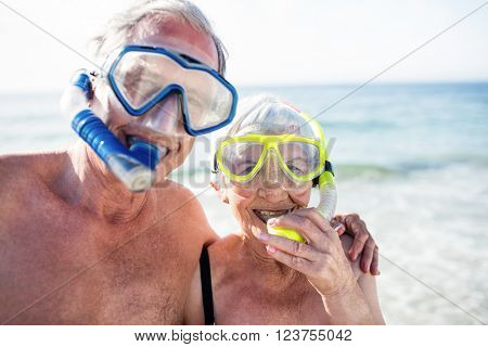 Portrait of happy senior couple with their diving mask at beach on a sunny day