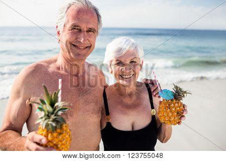 Portrait of senior couple holding pineapple cocktail on beach