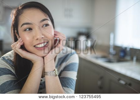 Happy young woman daydreaming in kitchen at home
