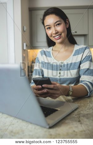 Portrait of happy woman typing a text message on her mobile phone in kitchen at home