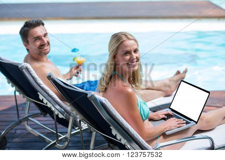 Portrait of happy couple sitting near pool with a laptop and martini glass